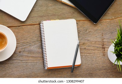 Top view image of open notebook with blank pages next to cup of coffee on wooden table.