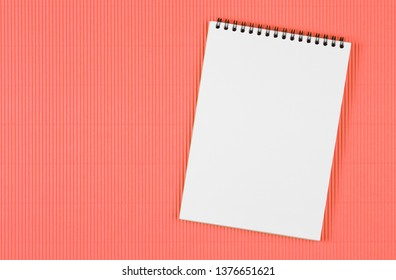 Top view image of  open notebook with blank pages. school notebook on Living Coral background, spiral notepad on a table, flat lay