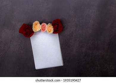 Top view image of an open notebook with blank pages near beautiful flowers on a clack background. Space for text. Planning a special event.  Establishing the diary with new tasks to do.