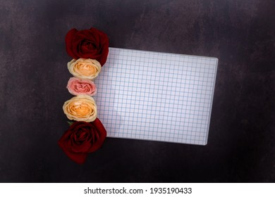 Top view image of an open notebook with blank pages with beautiful flowers on a clack background. Space for text. Planning a special event.  Establishing the diary with new tasks to do.