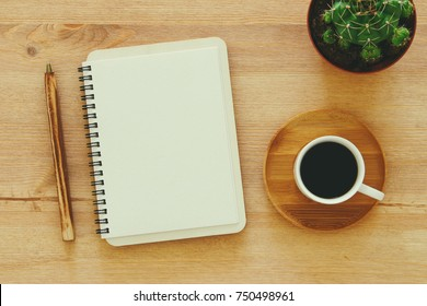 top view image of open notebook with blank pages next to cup of coffee on wooden table. ready for adding text or mockup