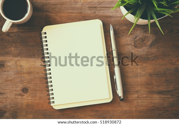 top view image of open notebook with blank pages next to cup of coffee on wooden table. ready for adding text or mockup. Retro filtered