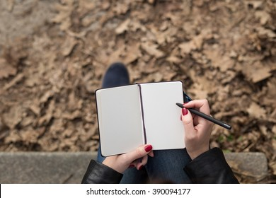 Top view image of open pad in female hands with pen sitting on stairs in the park. Blank sheets of small notebook overhead view