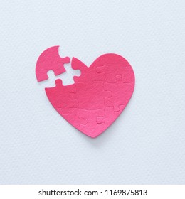 Top view image of paper pink heart puzzle with missing piece over white background. Health care, donate, world heart day and world health day concept