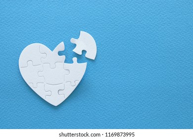 Top view image of paper white heart puzzle with missing piece over blue background. Health care, donate, world heart day and world health day concept
