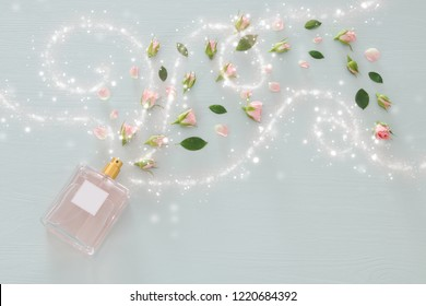 Top view image of perfume bottle with rose petals flowers over pastel blue background. Floral scent concept