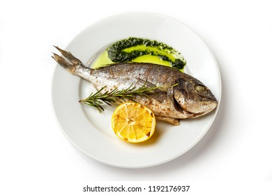 Top view image of plate with fresh grilled dorado fish and lemon isolated at white background.