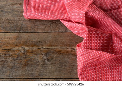 A top view image of a red and white tea towel on a wooden kitchen table.
