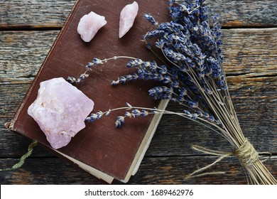 A top view image of rose quartz crystals on top of an old brown book with dried lavender flowers.
