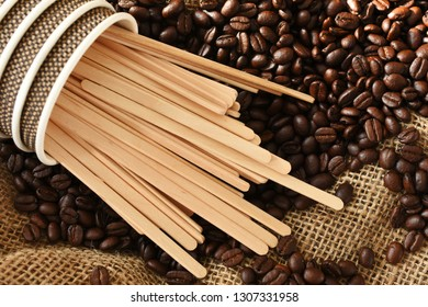 A top view image of several wooden stir sticks and roasted coffee beans.