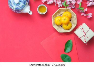Top view image shot of arrangement decorations Chinese new year & lunar holiday background concept.Orange wood basket & teapot with ornaments festive on modern red wallpaper at home office desk.