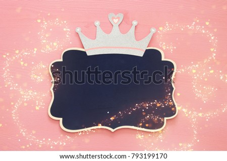 top view image of silver glitter crown and blackboard over pink wooden background