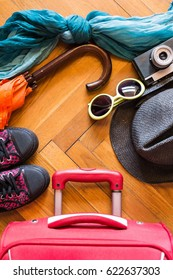 Top view image of suitcase, sunglasses, umbrella, sunhat, scarf, retro camera and sneakers on wooden floor background, travel concept