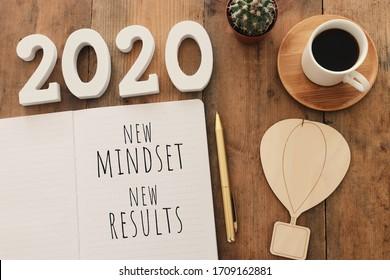 Top-View Bild von Tisch mit offenem Notebook und der Text neue Einstellung neue Ergebnisse. Erfolgskonzept und persönliches Entwicklungskonzept