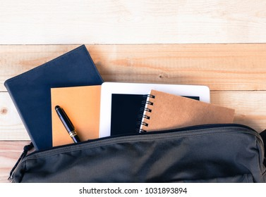 top view image of tablet, books and shoulder bag , student equipment on desktop concept