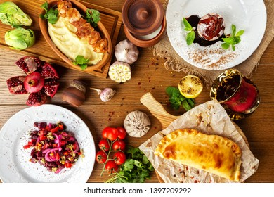 Top view image of traditional georgian lunch with various meals and ingredients at decorated wooden table background.
