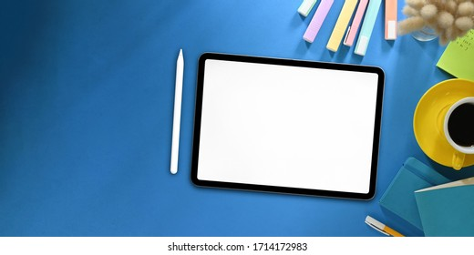Top view image of white blanks screen computer tablet with stylus pen putting on colorful working desk and surrounded by marker pens, wild grass, coffee cup, note and pen. Orderly workspace concept.