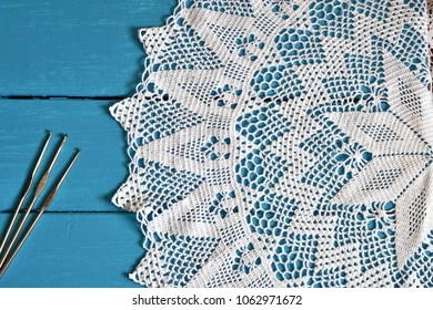 A top view image of a white crochet lace doily and three metal crochet hooks on a blue wooden background.