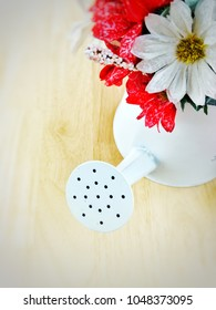 Top view image of white metal shower bucket decorated with artificial white and red flowers placed on wooden table with bright blurred space for add