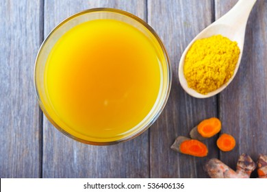 Top view of immunity boosting spicy turmeric power and juice on a wooden table.