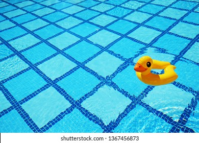 Top view of inflatable duck floating in an empty swimming pool with crystal clear water and blue square tile pattern background. Close up shot of rubber ring with a lot of copy space for text.