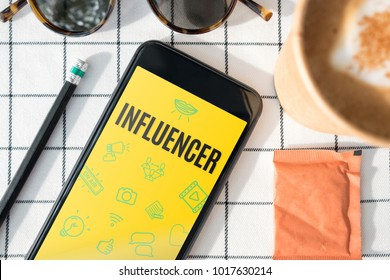 top view influencer feature on mobile screen with coffee cup,sunglasses,pencil on white table cloth.blogger lifestyle