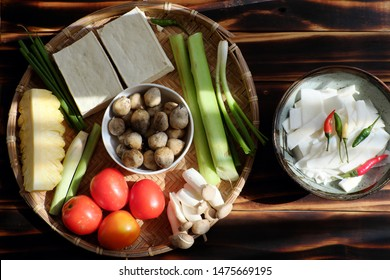 Top view ingredient food for vegetarian meal, vegetables soup from tomato, pineapple, bamboo shoot and tofu, mushroom cook with soy sauce, simple dish for vegan diet on wooden background