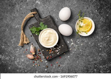 Top view of ingredients for homemade mayonnaise as eggs, lemon and spices on gray concrete background