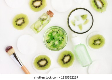 Top view ingredients Natural cosmetic for body care at home. Kiwifruit sliced and puree mask in jar with yogurt and lotion bottle. White and green colors.