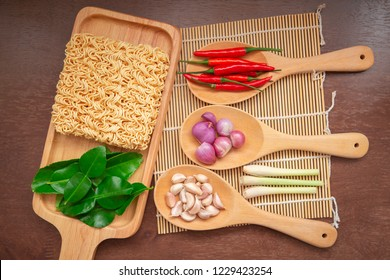 Top view instant noodles on wooden plate with seasoning or herbs,lime leaf,chilli,onion,lemon grass and garlic on wooden table