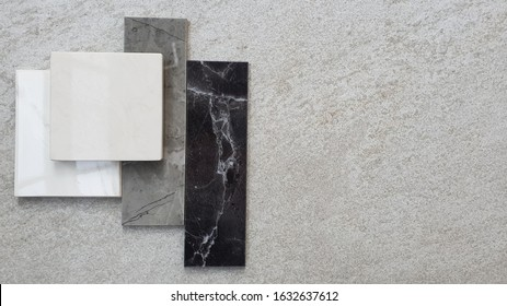 top view of interior stone tile samples material on cement background. the samples of marble stone place on grey stone background with space for text.
