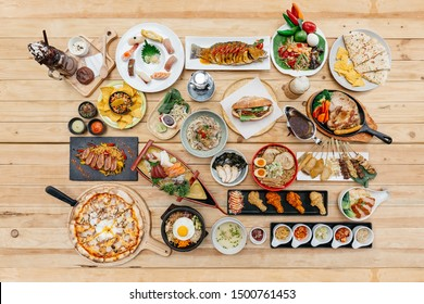 Top view of International Foods on wooden table include Sushi, Sashimi, Nachos, Spaghetti, Naan, Sandwich, Noodle, Steak, Ramen. Yakitori, Pizza, Bibimbap, Fried Chicken Wings, Brownie Frappe.