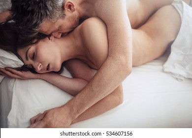 Top view of intimate lovers making love in bed. Romantic and passionate young couple on bed having sex.