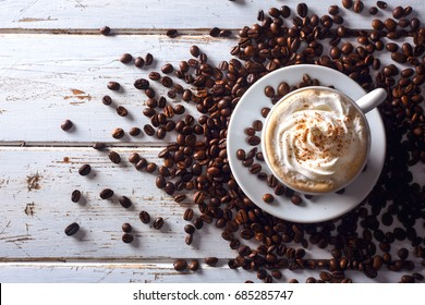 Top view of an irish coffee in a cup with coffee beans around over a white wood table