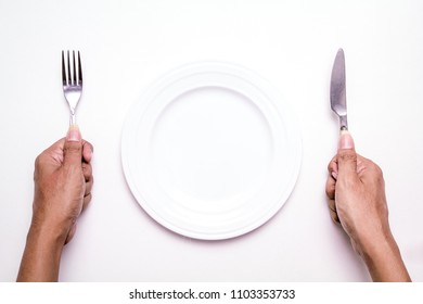 Top View of Isolated Empty Plate with Hands Holding Cutlery on White Background, Ready to Eat