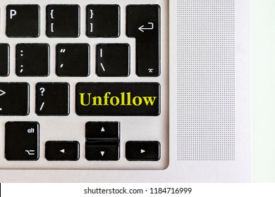 "top view isolated laptop keyboard with yellow ""unfollow"" text on button, concept design"