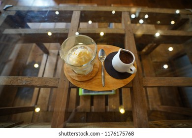 Top view of Italian dessert Affogato, a scoop of ice cream and espresso shot on glass coffee table reflecting light