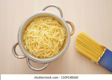 top view of italian dried and boiled noodles on white wooden table