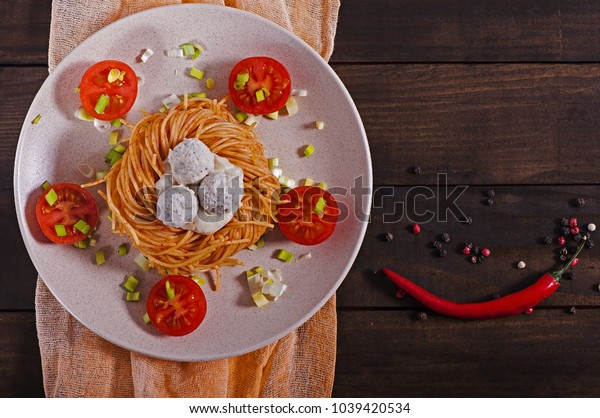 Top view of Italian pasta with white sauce, cherry tomatoes and meatballs on a white plate.