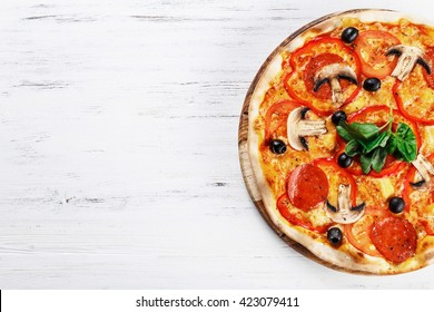 Top view of Italian rustic PIZZA with mushrooms, basil, tomato, olives and cheese and bacon. WITHOUT one piece.  white wooden table background. Look as Prosciutto, Capricciosa, Funghi, Cotto PIZZA.