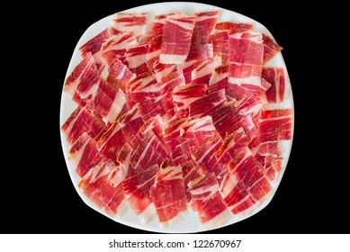 Top view of jabugo ham white plate with slices over black background
