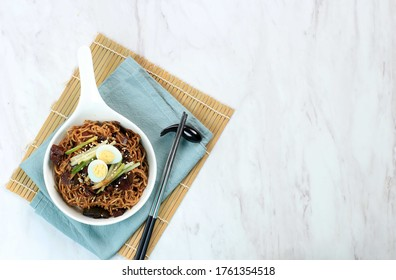 Top View Jajangmyeon or JJajangmyeon  is Korean Noodle with Black Sauce. Topping with Quail Edd, Cucumber, Sesame Seed, and Spring Onion. Copy Space on Left Side