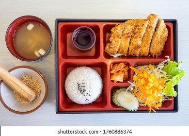 Top view of Japanese Bento Box with deep fried pork cutlet (tonkatsu set), salad and sauce. Seaweed soup