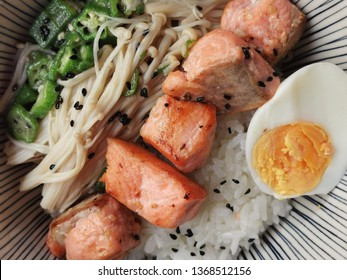 Top view Japanese style healthy rice bowl. Grilled salmon dices, stir-fried chopped okra and golden needle mushroom and hard boiled egg. Sprinkle with black sesame.