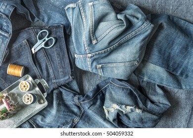 Top View of Jeans and Sewing Tools with Copy Space on Blue Fabric Background