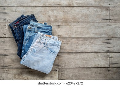 Top view, Jeans stacked on a wooden background.