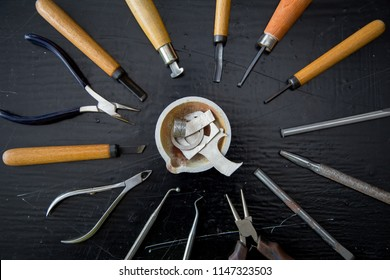 Top view jeweller's tools - pliers, cutters, carving knives, moulds, raw silver  pieces, engraver, sander, jeweler's bench pin