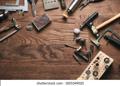 Top view jewelry maker workbench with tools on table. Equipment and tools of a goldsmith on wooden working desk inside a workshop.