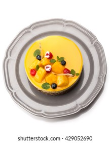 Top view of Joconde Imprime Mango and Passion fruit Mousse Cake, decorated with fresh fruits and berries