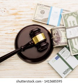 Top view Judge's gavel and packs of dollars and euro banknotes on a white wooden table.The concept of growing national debt- image